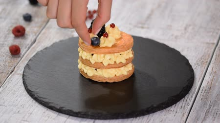 blackberry : Pastry chef making French Mille Feuille with custard and berries. French dessert millefeuille of puff pastry and custard cream.