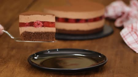взбитые : Piece of delicious chocolate mousse cake with raspberries jelly. Стоковые видеозаписи