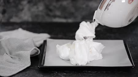 pavlova : Putting meringue on the baking sheet. Pastry chef prepares meringue roll cake.