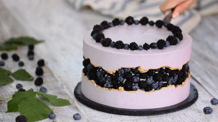 šlehačka : Female hands cutting a piece of cake. Purple beautiful cake decorated with berries, blackberries and blueberries. Dostupné videozáznamy