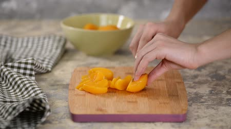 enlatamento : Cut canned peach on a wooden cutting board. Vídeos