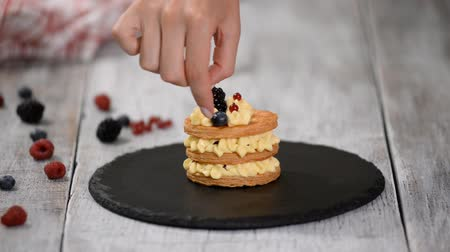 pasta sfoglia : Pastry chef making French Mille Feuille with custard and berries. French dessert millefeuille of puff pastry and custard cream.