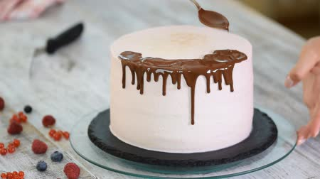 çırpılmış : Baker pours liquid chocolate. Confectioner-baker decorate big beautiful cream cake.