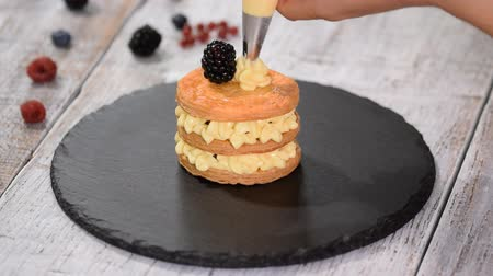 amoras : Pastry chef making French Mille Feuille with custard and berries. French dessert millefeuille of puff pastry and custard cream.