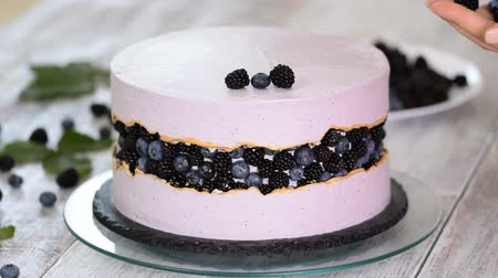 чизкейк : Confectioner decorates a beautiful cake with blueberries and blackberries.