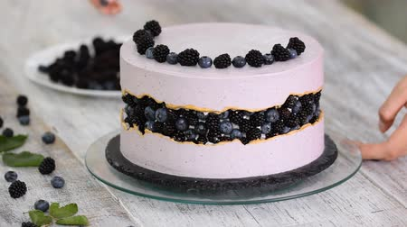 blackberry : Confectioner decorates a beautiful cake with blueberries and blackberries.