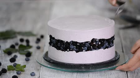 blackberry : Confectioner in the kitchen makes a sponge cake with berry cream. The concept of homemade pastry, cooking cakes.