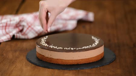 açoitado : Woman decorating and sprinkling nuts on top chocolate mousse cake.