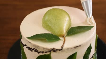 pears : Decorating a cake with cream using piping bag. Woman confectioner makes cake with pear.