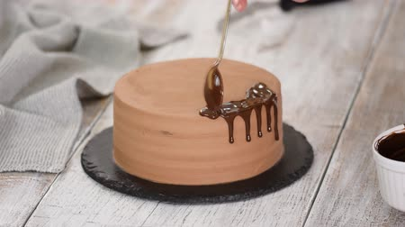 Glazing chocolate cake with melted chocolate. Woman pouring chocolate over cake. Homemade cocoa layered cake.