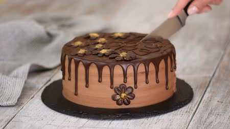 yermantarı : Confectioner hands cut by knife chocolate cake decorated with flowers.