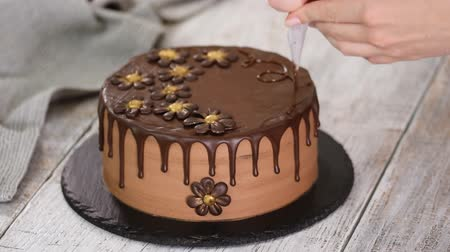 Confectioner-baker decorate beautiful cream cake with melted chocolate.