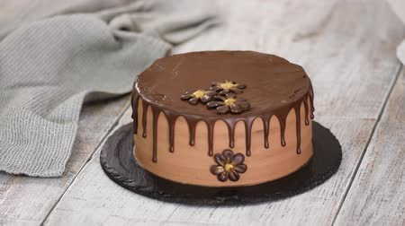 Confectioner-baker decorate beautiful cream cake with chocolate flowers.