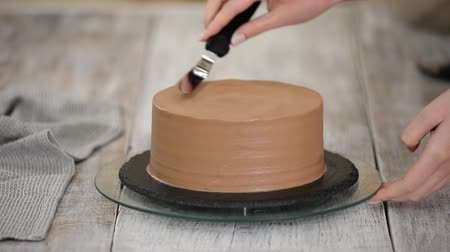 námraza : Young Woman Is Decorating Chocolate Cake, Standing In Home Kitchen. Woman finishes frosting chocolate cake. Dostupné videozáznamy