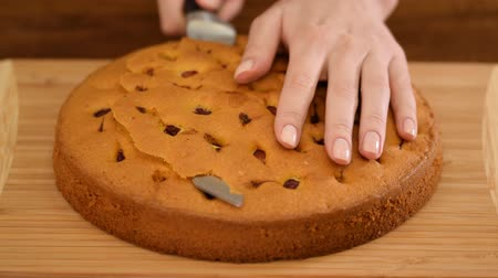 Womans hands cut the top of a cherry sponge cake.