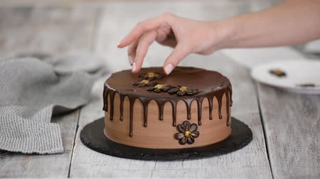 アイシング : Confectioner-baker decorate beautiful cream cake with chocolate flowers.