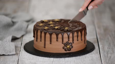 pite : Confectioner hands cut by knife chocolate cake decorated with flowers.