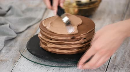 yermantarı : Step by step. Pastry chef making chocolate layer cake with prune filling. Confectioner puts cream on top of cake.