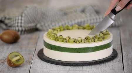 pite : Cutting homemade mousse cake with kiwi.