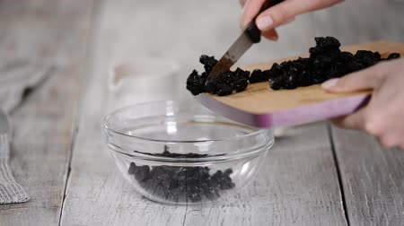 Female hands put dried prunes into a bowl. Healthy eating concept.