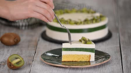pite : Eating piece of homemade mousse cake with kiwi. Stock mozgókép
