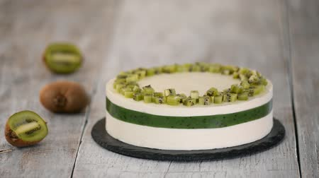 pite : Chef decorate the cake with fresh kiwi. Homemade mousse cake with kiwi. Stock mozgókép