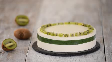 Chef decorate the cake with fresh kiwi. Homemade mousse cake with kiwi. Stok Video