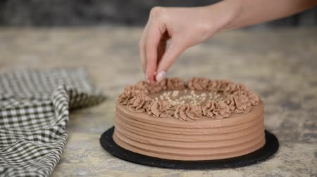 Close-up of sprinkle nuts on a cream of a chocolate sponge cake. Baker decorated chocolate cake with nut.
