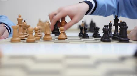 zkontrolovat : hands of a two chess players and black queen take white queen