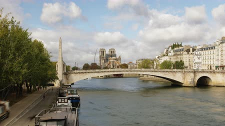 リベット : Paris bridge behind notre dame de paris cathedral time lapse of the rebuilt with boats on the seine river and people walking