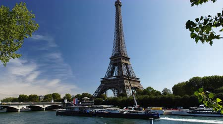リベット : Eiffel tower time lapse view in Paris France with boats passing on the Seine shore during a sunny summer day