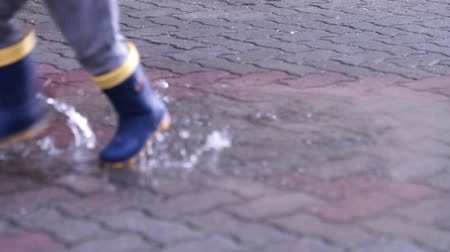 Child with rubber boots jumping into a puddle Stock Footage