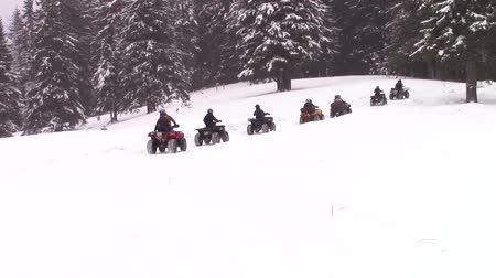 atv : Group of quads or ATVs riders on a mountain trail in winter
