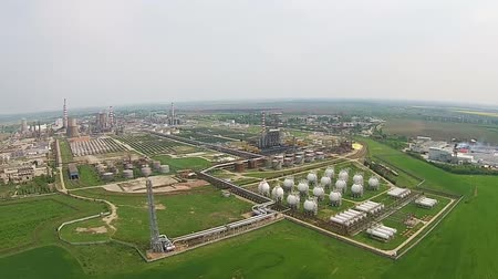 industrialization : Modern oil refinery with array of natural gas reservoirs and tall metallic tower for exhaust gases burning aerial panning Stock Footage