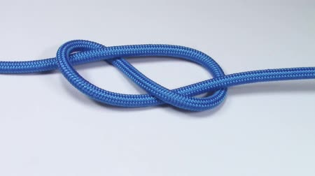 cordas : Figure eight knot made from blue synthetic rope, tightening on white background