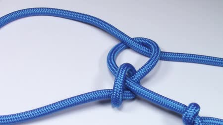 corda : Common cowboys lasso knot made from blue synthetic rope, tightening on white background Stock Footage