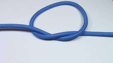 cordas : Simple overhand knot made from blue synthetic rope, tightening on white background
