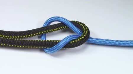 tying : Reef knot made from two different synthetic ropes , tied on white background