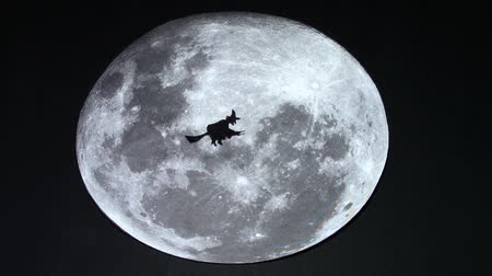 süpürge : Paper cut witch silhouette slowly flying on her broom in front of the moon, going on her nightly workings