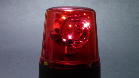 syrena : Red emergency beacon closeup with rotating mirrors , against a black background