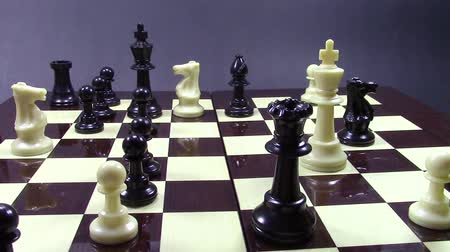 király : Complex position at chess game, while black queen is moving to squares on the board ending the game by checkmating the white king Stock mozgókép