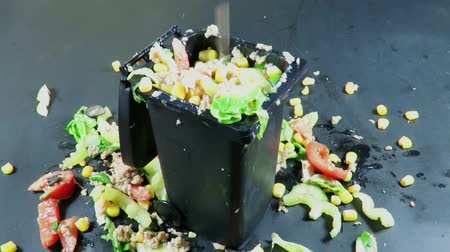 atık : Food is thrown over a salad filled plastic trash can container , creating a mess all around, conceptual footage about modern food waste, against a black background