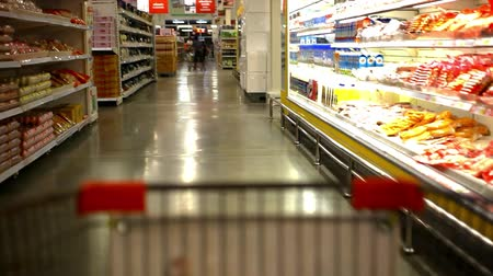 grocery : Customer shopping at supermarket with trolley and cleaning lady cleans market. Video shift motion time lapse speed up