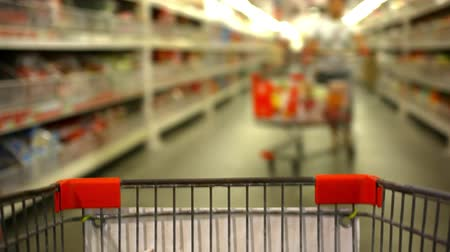 lojas : Customer shopping at supermarket with trolley and blurred background. Video shift motion time lapse speed up Vídeos