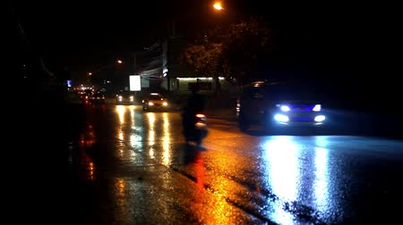 noite : Cars and motorbikes driving on a wet road at night after rain. Video