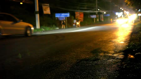 kuyruk : Cars and motorbikes driving on a wet road at night after rain. Video
