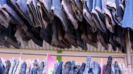 bolso : Close up of many blue jeans hanging on a rail. Video macro shift motion