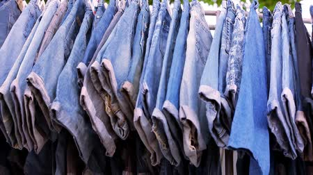 clothing : Close up of many blue jeans hanging on a rail. Video macro shift motion