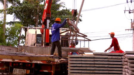 metal worker : KOH SAMUI, THAILAND - JUNE 21: Crane activity at construction site, workers carry concrete slabs.