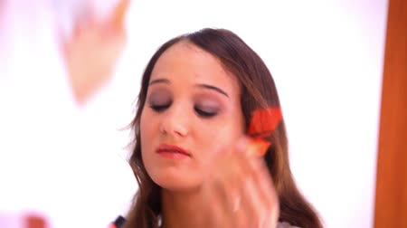 plucks : Beautiful young woman plucking eyebrows paints lips and looking, preens at mirror. Video time lapse speed up